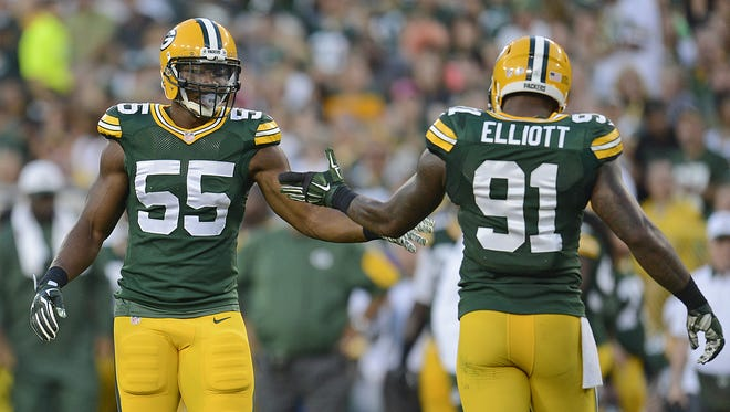 Green Bay Packers outside linebacker Andy Mulumba (55) celebrates a play with linebacker Jayrone Elliott (91) against the New Orleans Saints during Thursday night's preseason game at Lambeau Field.