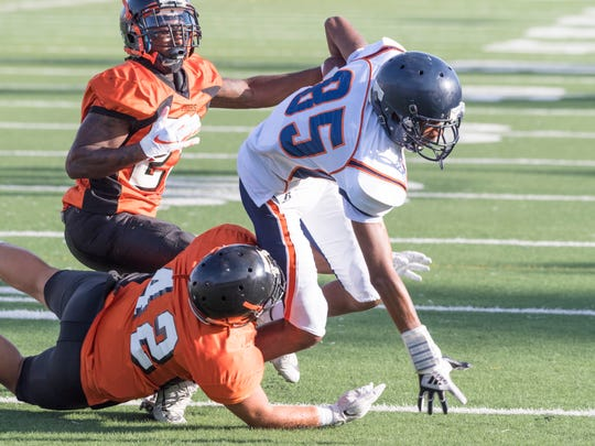 College of the Sequoias' Kaleb Wilson scrambles away from Reedley College defenders in a scrimmage on Tuesday, August 21, 2018.