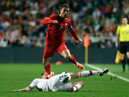 FILE - In this June 7, 2013, file photo,  Portugal's Cristiano Ronaldo gets the ball past Russia's Alexei Kozlov, on the ground, during their 2014 World Cup qualifying group F soccer match, at the Luz stadium in Lisbon. (AP Photo/Armando Franca, File) - SEE FURTHER WORLD CUP CONTENT AT APIMAGES.COM
