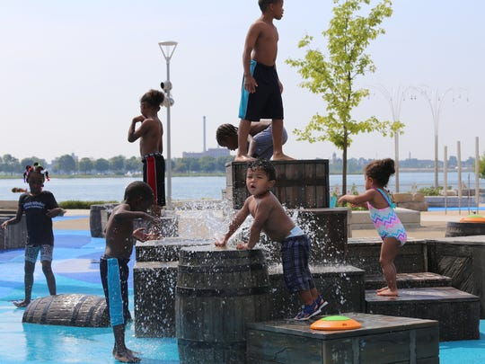 Kashis Duckett, 2, controls the out water coming out of the barrel as he has fun getting wet and staying cool with the other kids on Wednesday, July 29, 2015, at Mt. Elliott Park  & Pavilion that features a Great Lakes schooner-themed water park in Detroit along the Detroit River.