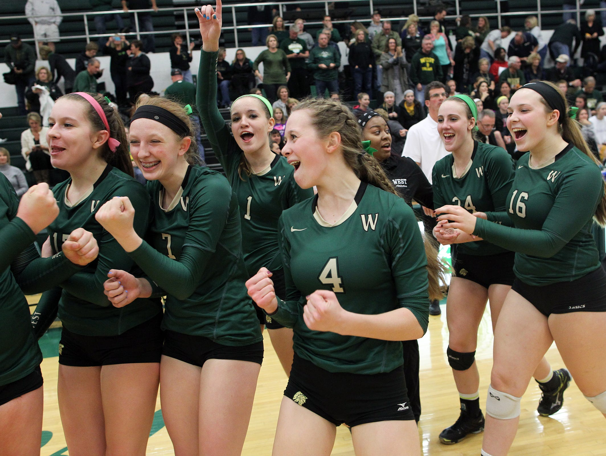 West High teammates celebrate their regional semifinal win over City High at West High on Thursday, Oct. 29, 2015.