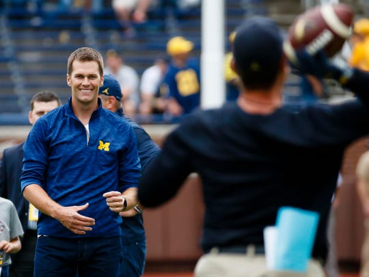 New England Patriots quarterback Tom Brady and Michigan Wolverines head coach Jim Harbaugh pass the ball around during warm ups prior to the game against the Colorado Buffaloes at Michigan Stadium on Sept. 17.