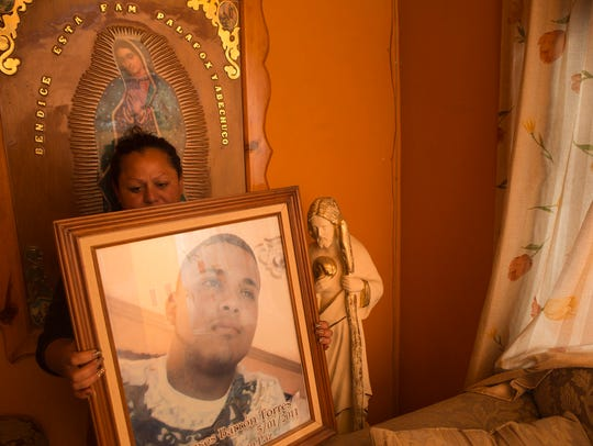 Rosa Elena Avechoco  holds a picture of Ramses Barron