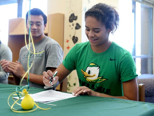 Keira McCarrell signs a letter of intent to be on the track team at the University of Oregon during a signing day ceremony for eight student athletes at West Salem High School on Wednesday, Nov. 9, 2016.