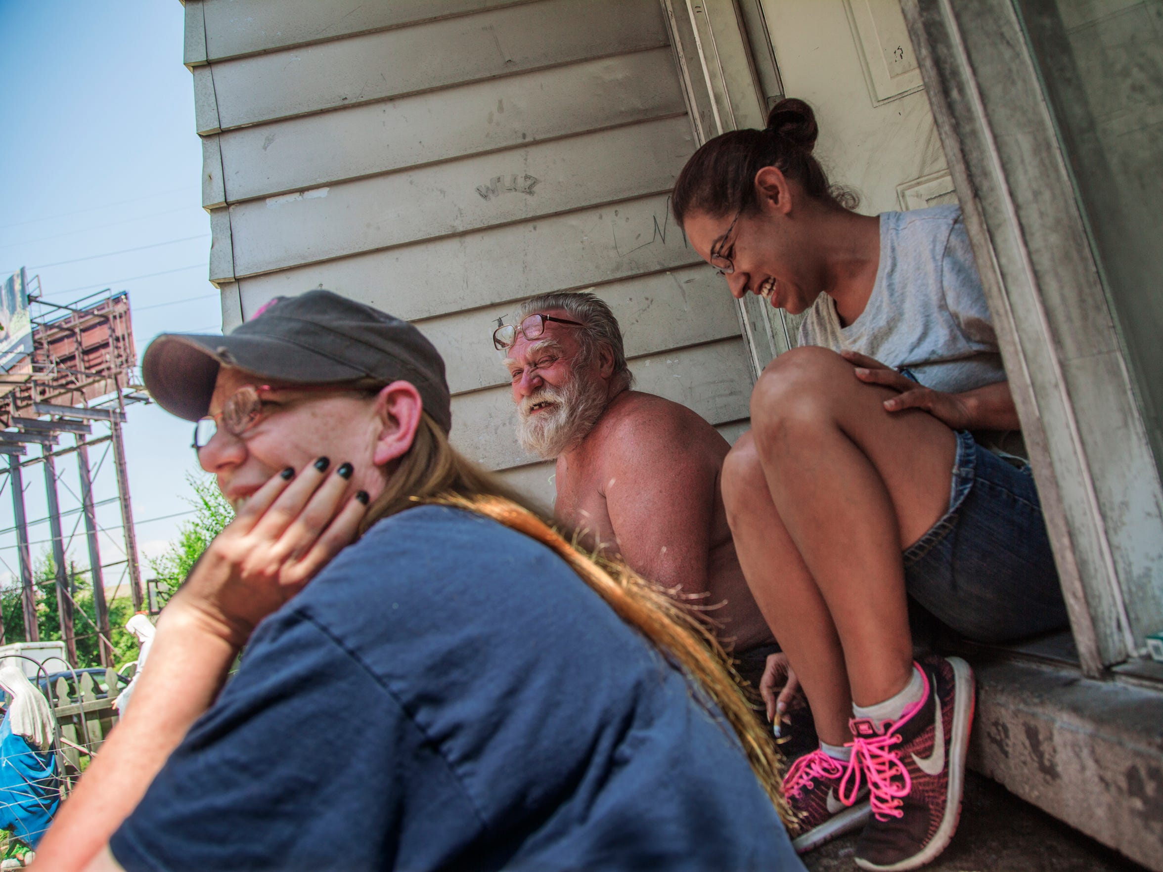 """Your neighbors become your family,"" said Lisa Roland, right, about her neighborhood and the city's offer to move Delray residents to a new house elsewhere in the city. ""They watch out for you, they watch out for your kids, they watch out for your house, your cars. We take care of one another. You don't find that every time in every neighborhood."" She was sitting with family friend Kim Libra, 52, and Mike Donovan, 73, on the porch of the Donovan family's house on July 18, 2017."