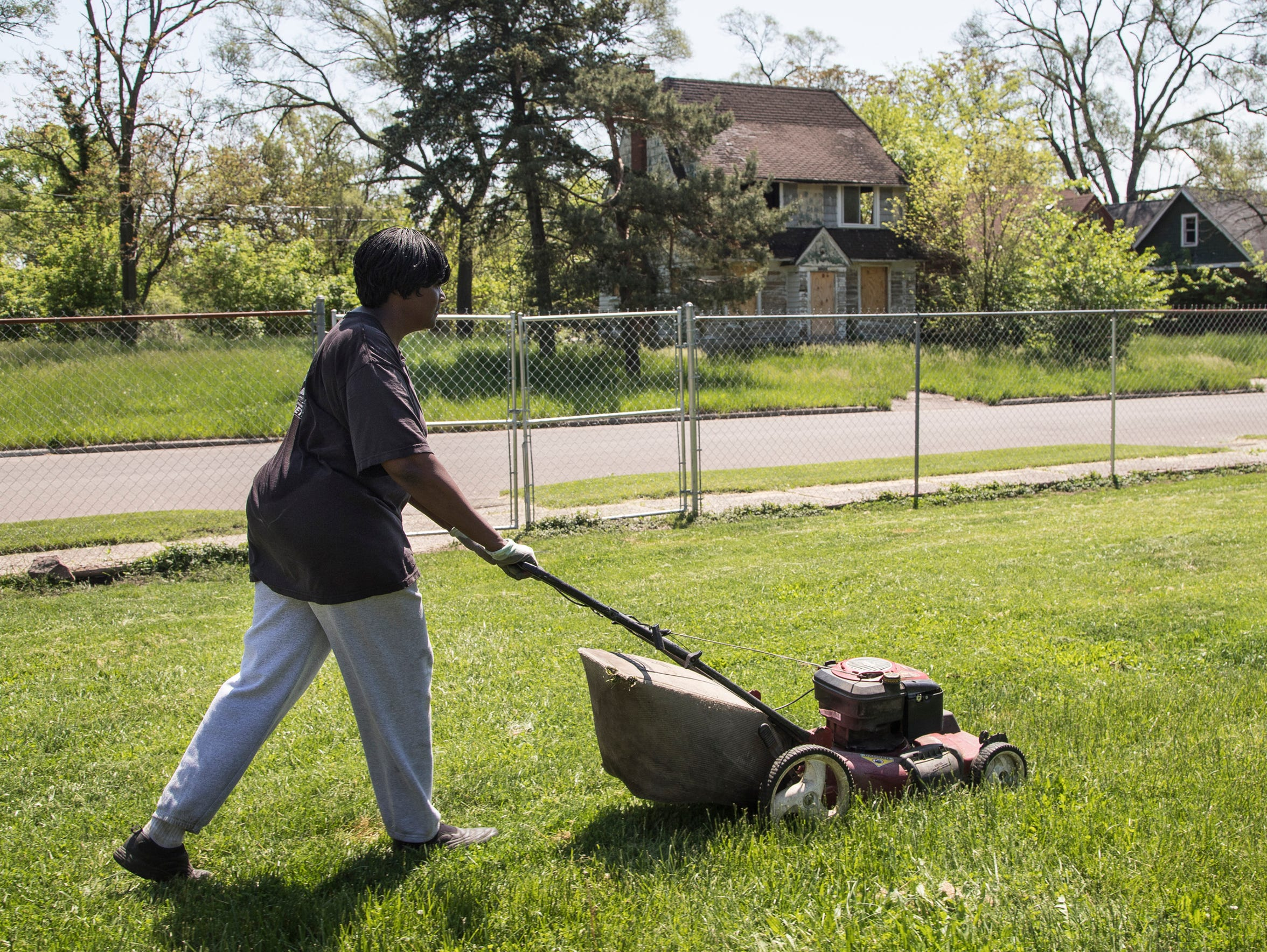 Anna Hollins in May mows the yard of her Lauder Street home, which sits across from a land bank house investigated for possible dog fighting. (Photo taken May 25, 2018)