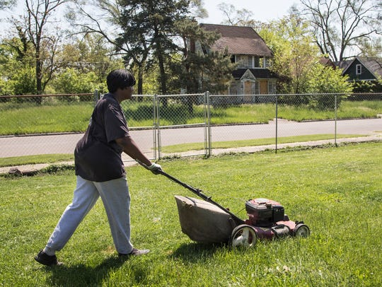 Anna Hollands mows the yard of her home on Lauder which