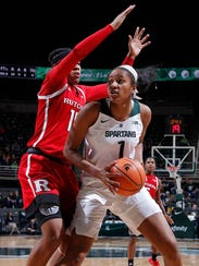 Michigan State's Sidney Cooks (right) maneuvers for a shot against Rutgers' Caitlin Jenkins on Sunday, Dec. 31, 2017, in East Lansing, Michigan.