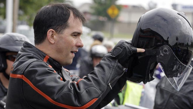 Gov. Scott Walker puts on his helmet before riding his Harley-Davidson during a leg of Ride with Walker in Sheboygan.