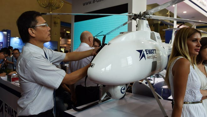 A man takes close-up photos of the inside of a drone at an exhibition of unmanned aerial vehicles in Beijing on July 10. Members of the drone industry are worried that other countries will develop aircraft faster because of restrictive rules in the United States.