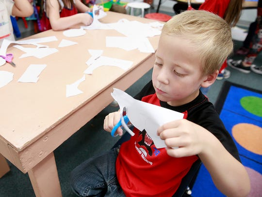 Raymond Ferrier works on a project in Phyllis Cox's kindergarten class on Wednesday at Lydia Rippey Elementary School in Aztec.