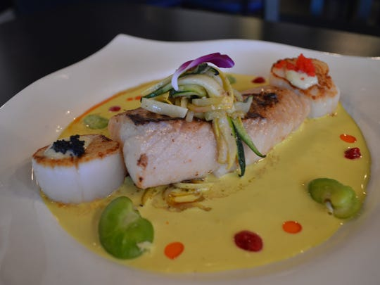Miso-marinated black cod and seared scallops with julienned vegetables in a coconut lemongrass sauce from Fish Tale Grill in Cape Coral.