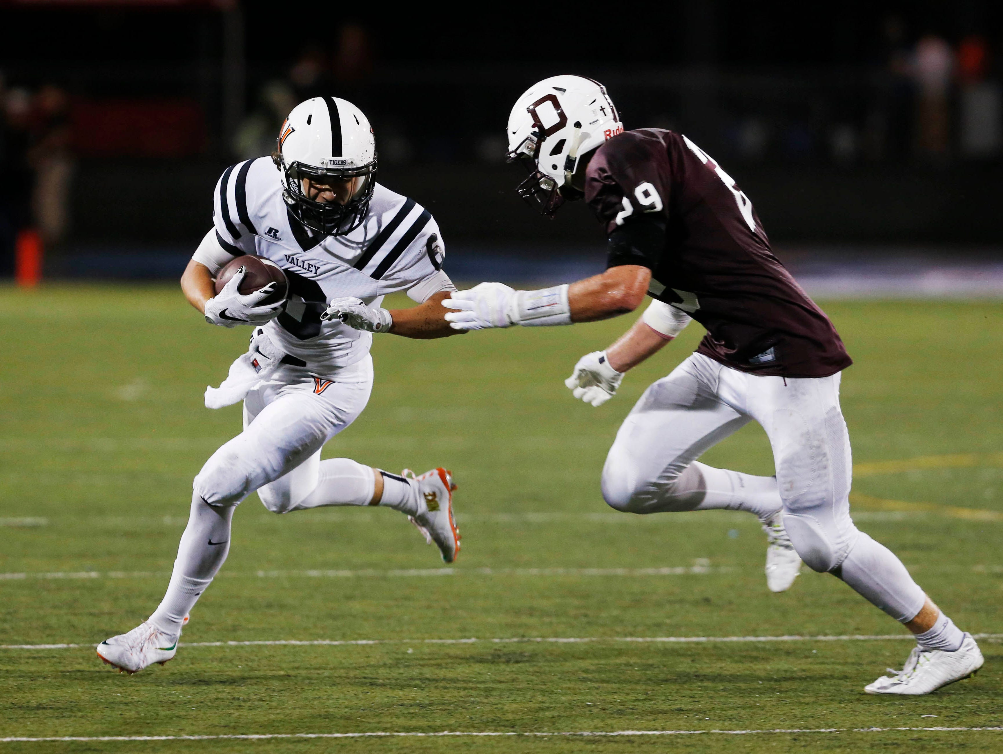 Valley's Braeden Heald (6) tries to manuever around Dowling Catholic's Jacob Shedenhelm (29) Friday, Sept. 18, 2015, at Drake Stadium in Des Moines.