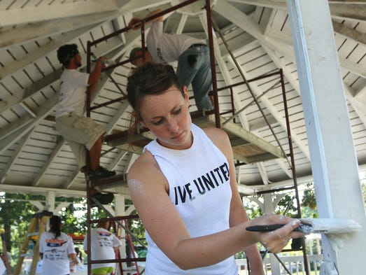 Shelbi Dixon, a student at Cox College, helps paint a gazebo  in Washington Park as their Day of Caring project.