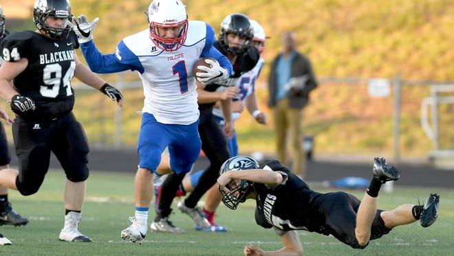 West Henderson's Elijah Nickell avoids a tackle from North Buncombe's Lee Ballard as he runs the ball during the first half of their game at North Buncombe High School on Thursday, Sept. 7, 2017. The Falcons defeated the Blackhawks 42-7.