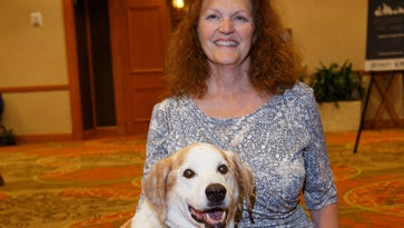 Alicia Smith, who represents the National Alliance on Mental Illness on a Transportation Department committee, is shown July 7, 2016, with her service dog Hunka at a NAMI conference in Denver.