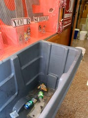 Far left: Rainwater from a first-floor ceiling and display case accumulates in a large trash container at Delsea Regional High School after heavy rainfall flooded sections of the building on Thursday.