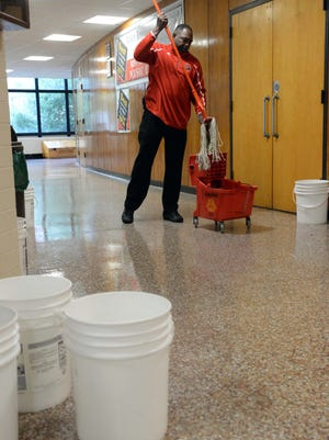 Left: Vince Driver, an employee of Delsea Regional High School, mops a hallway floor after heavy rainfall flooded sections of the building on Thursday.