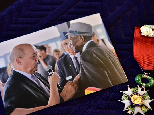 A copy photo of Austin Powlis receivingthe Legion of Honor from French Defense Minister Jean-Yves Le Drian in 2015, along with the actual medal to the right.