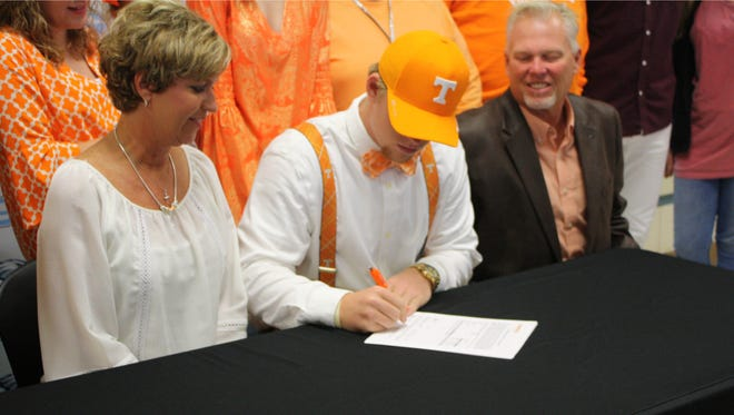 Gibbs senior Bass Cooper signs his letter of intent to play baseball at Tennessee on Wednesday with his parents, Michele Davis and Blu Cooper, looking on.