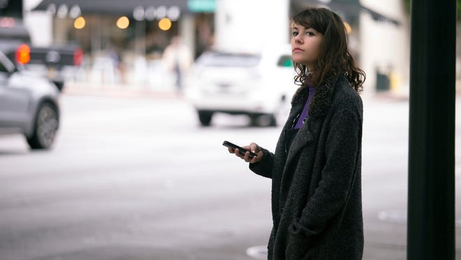 A woman waits by the road with her smartphone.