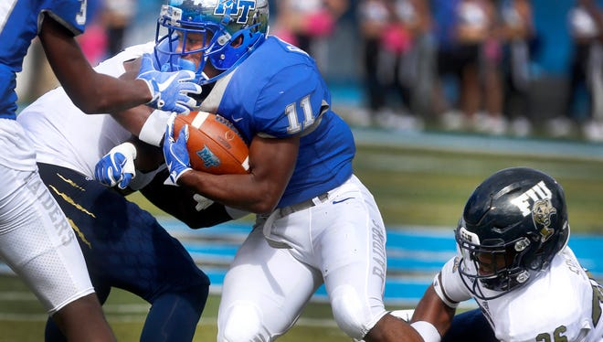 MTSUÕs Brad Anderson (11) runs the ball as FIUÕs Brad Muhammed (27) and Shermarke Spence (26) try to stop Anderson during the game, on Saturday, Oct. 7, 2017, at MTSU.