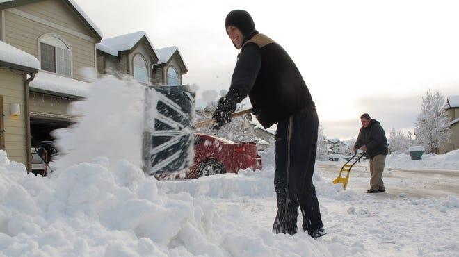 Gregg Schneider, left, and Mathew Cornett clear snow from their driveways in Bellemont, Ariz., on Dec. 20.