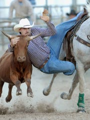 Tim Robertson of Flushing jumps from his horse and grabs a steer during a rodeo steer-wrestling competition at the St. Clair County 4-H and Youth Fair in Goodells County Park.