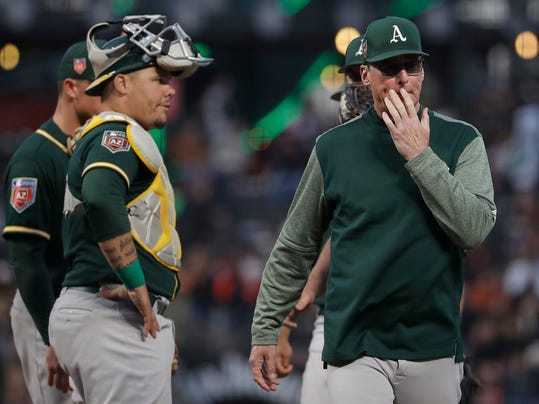 Oakland Athletics manager Bob Melvin, right, walks toward the dugout after meeting with catcher Bruce Maxwell, left, and other players on the mound during the fourth inning of a spring baseball game against the San Francisco Giants in San Francisco, Tuesday, March 27, 2018. (AP Photo/Jeff Chiu)