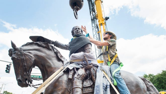 Sorin Hutzelman, of the Inferno Art Foundry, mounts the Galvez statue in order to hook it up to the crane before hoisted it into place at the corner of North Palafox and Wright Streets in downtown Pensacola on Tuesday, April 24, 2018.  The official unveiling of the statue will take place on May 8th.