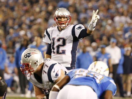 New England Patriots quarterback Tom Brady motions