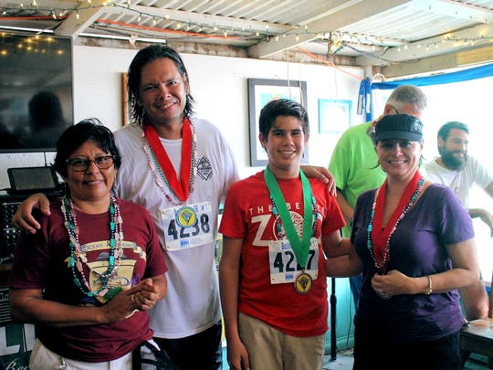 Ocean Academy Principal Hilda Mann, left, with Mathew Sandoval, Student Council President, second from right, and two ex-pats who participated in the Caye Caulker Go Slow Run off the ocast of Belize, presented by Capt'n Fun Runners to raise money for the school.