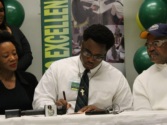 Menard's Vincent Sampson signs with Jackson State Wednesday.