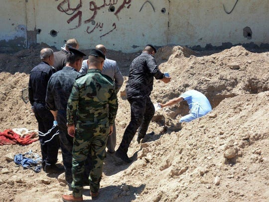 Iraqi security forces work at the site of a mass grave,