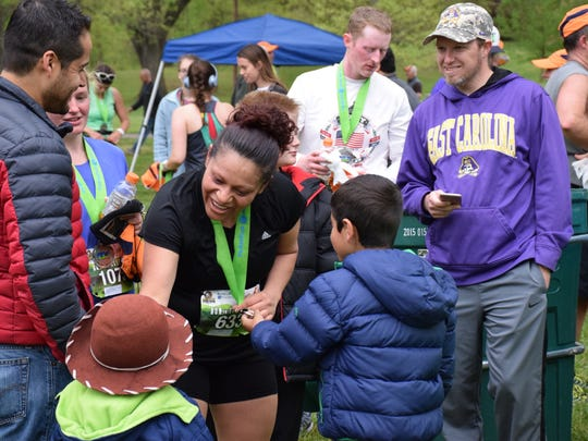 Silvia Garcia-Romero of Harrisonburg shows her finishers medal to family members after running the Park-to-Park Half Marathon at Ridgeview Park in Waynesboro on Saturday, April 30, 2016.