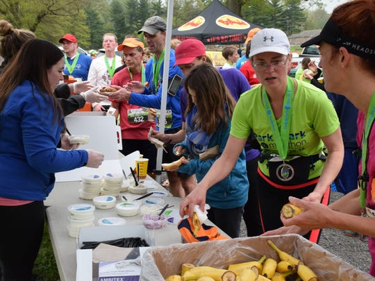 Volunteers hand out bagels donated by Panera Bread and bananas to competitors after the Park-to-Park Half Marathon at Ridgeview Park in Waynesboro on Saturday, April 30, 2016.