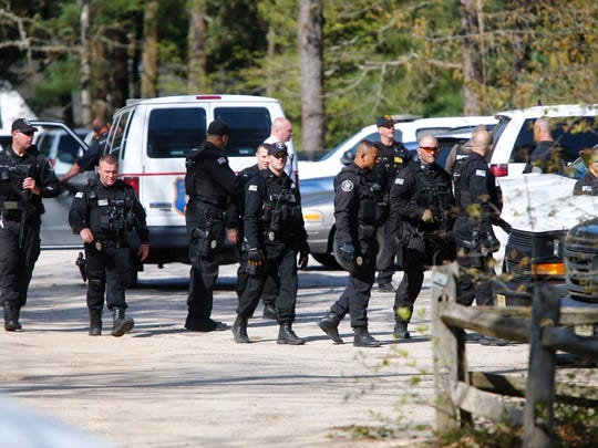 Department of corrections special operations officers gather at double trouble state park before heading out on a search Monday morning.