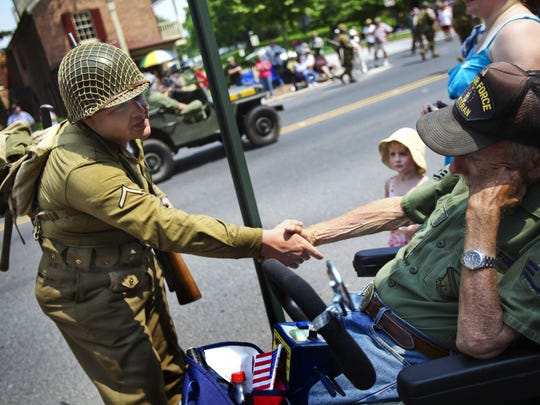World War II re-enactor Rod Pellegrini stops to shake the hand of Vietnam Air Force veteran Bill Claik on Baltimore Street during the Gettysburg Veterans Memorial Day Parade.
