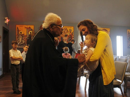 Bishop Saydina Antoun blesses Laura Wilson and her daughter Mary on Friday evening at St. Nicholas Orthodox Church.