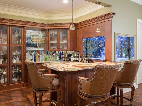 The family room has a bar with an onyx surface and built-in cabinets with glass doors.