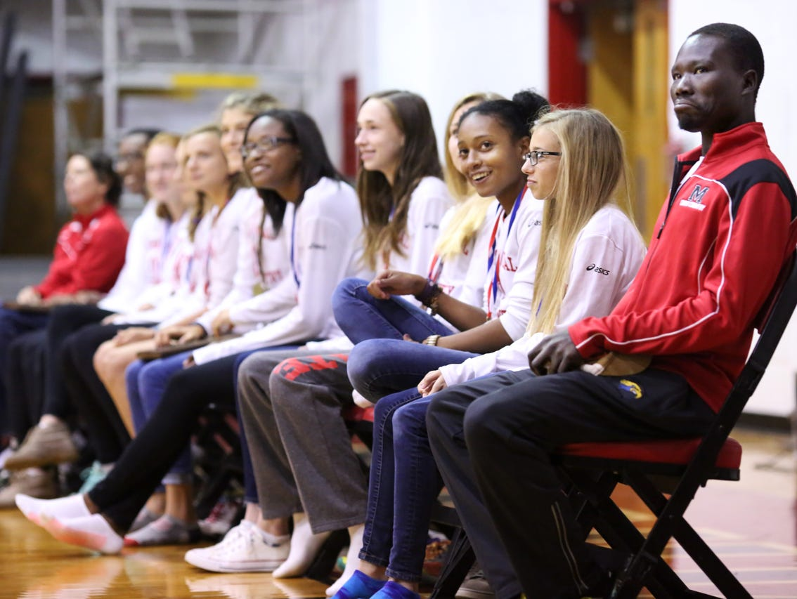 Rizik Lado, assistant cross country coach at duPont Manual High School, sits with team members during a pep rally. November 9, 2016