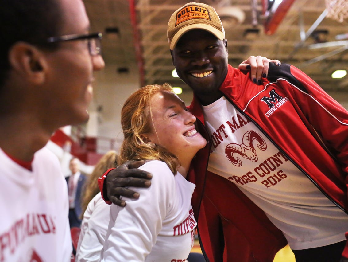 Rizik Lado, assistant cross country coach at duPont Manual High School, talks to Emma Kuntz and Yared Nuguse during a pep rally celebrating the recent cross country state championship victory. November 9, 2016