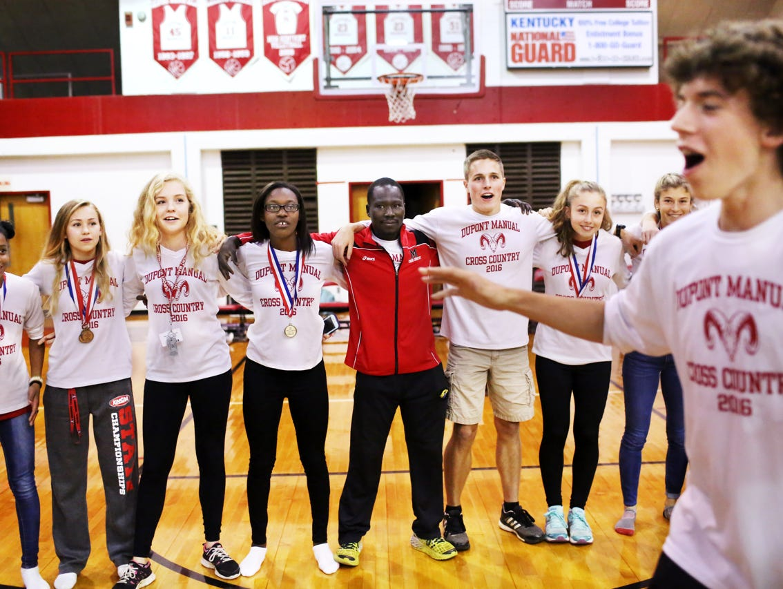 Rizik Lado, center, assistant cross country coach at duPont Manual High School, celebrates the recent cross country state championship with team members at a Pep Rally. November 9, 2016