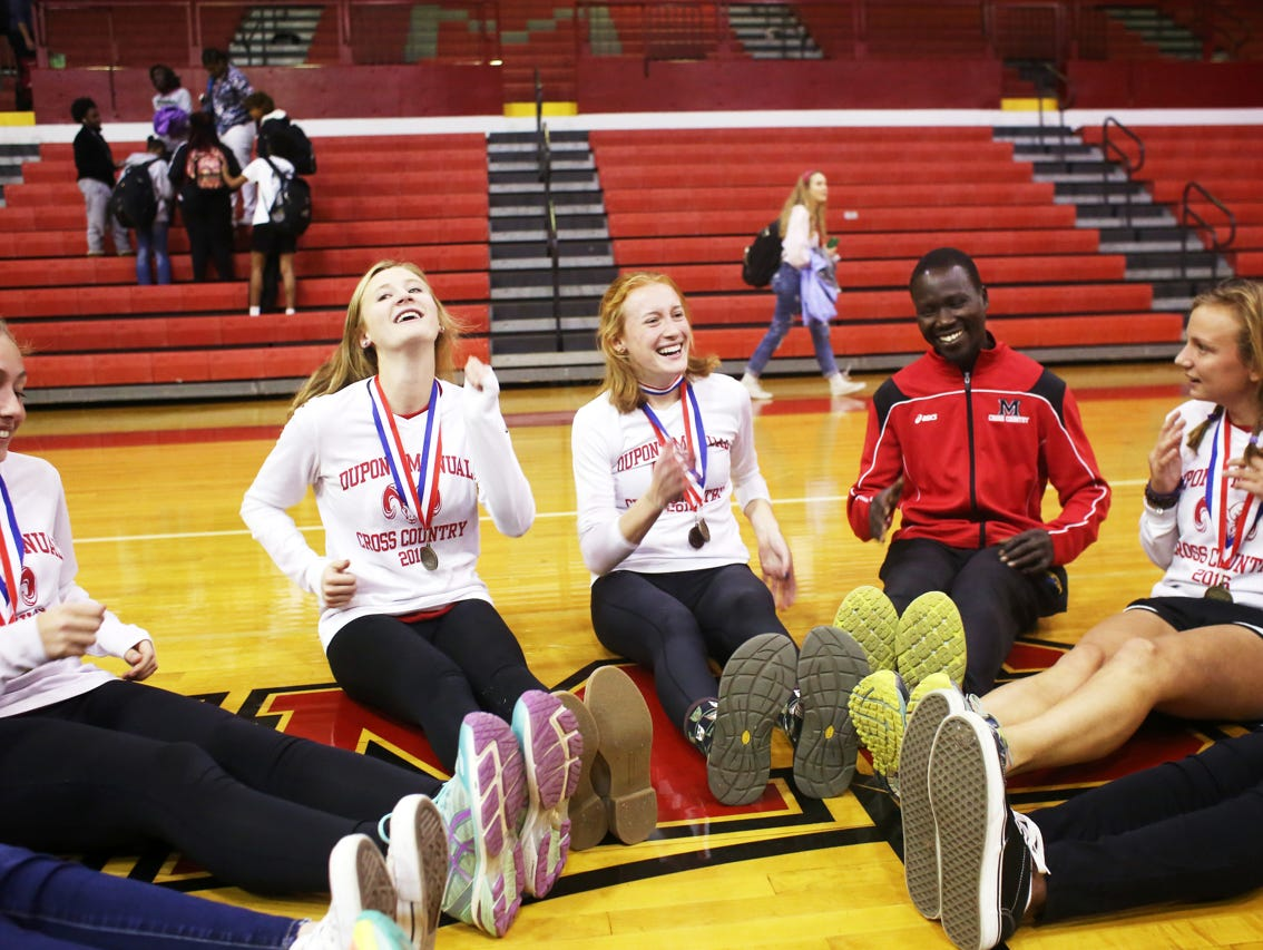 Rizik Lado, assistant cross country coach at duPont Manual High School, leads a warmup exercise with team members, left to right, Maeve Watts-Roy, Grace DuPlessis, Emma Kuntz, and Jordan Grantz after a pep rally celebrating the recent cross country state championship victory. November 9, 2016