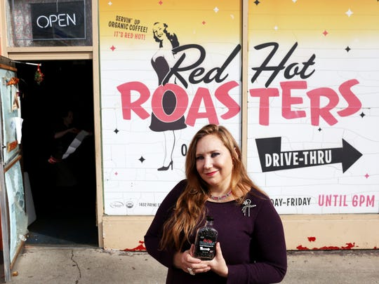 Sondra Powell, one of the Red Hot Roasters owners, poses outside the store showcasing a 2.5 oz single serving portion of bourbon barrel-aged coffee beans at her store on Lexington Avenue.Powell just started selling the speciality beans, using lighter bodied coffee bean from Central America to compliment the oaky, vanilla and caramel flavors from the bourbon oak barrel. December 5, 2016 Tyler Bissmeyer/Special to The C-J