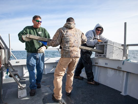 Capt. Monty Hawkins (left), Dan Iacangelo and Frank Stuernagle (right) dropping cement for reef building off the coast of Ocean City.