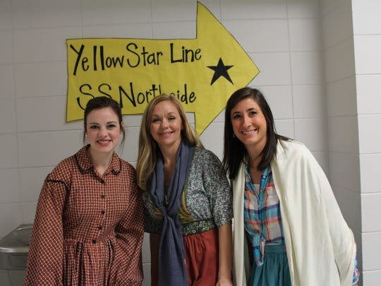 """Ms. Collins, Mrs. Reitano and Mrs. Hightower pose before they begin the process of interviewing the """"immigrants."""""""