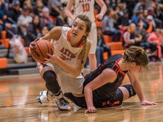 Aztec's Reigan Weaver secures a loose ball against Durango, Colo., on Saturday at Lillywhite Gym in Aztec.