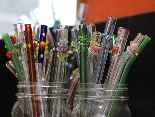 Daedra Surowiec decorates glass straws with swirls,