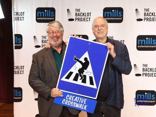 """Stevens Point Mayor Mike Wiza, left, shows off his city's Creative Crosswalk sign to """"Monty Python"""" actor and comedian John Cleese backstage at the Weidner Center on Monday night."""